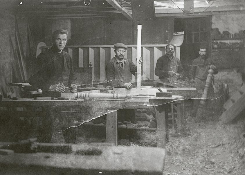 """Alfons Lerouge (tweede van links) geflankeerd door zijn werklieden in het atelier achter het """"Estaminet Lerouge"""" te Ooigem."""
